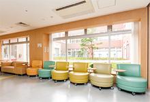 病棟内にある、パステルカラーがかわいらしいソファー。窓の外には中庭が