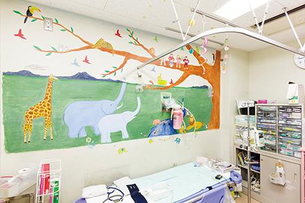 診察中子どもたちが怖がらないようにと、壁には動物たちの絵をあしらっている。反対側の壁にはクジラも