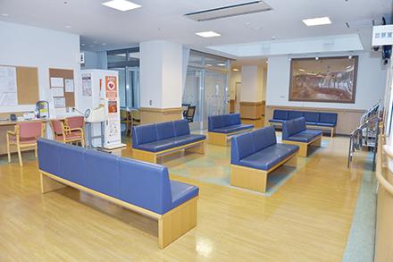 愛和病院の待合室。受付スタッフが明るく元気なあいさつで迎える