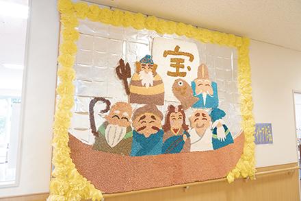 1階には色紙を筒状に丸め、多数のピクセルにして作られた七福神の作品が飾られている。通所リハビリテーション利用者が作業療法で作成
