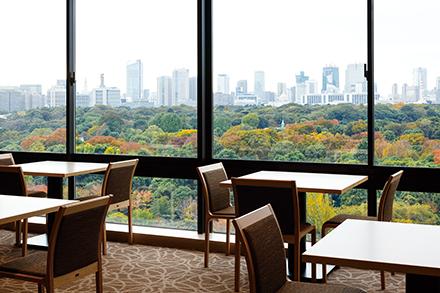 足下までの広い窓ガラス越しに望む、北の丸公園と高層ビル群とのコントラスト