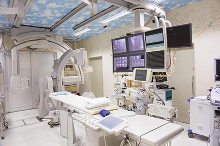 先端機器のそろうカテーテル治療室。天井に描かれた青空が、患者の緊張を和らげる