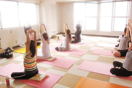 ゆっくりと呼吸しヨガのポーズを取ることで腰痛や肩凝りの改善を試みる人気の教室