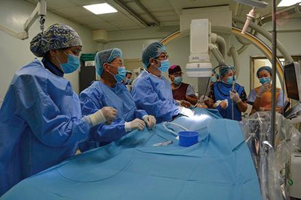 モンゴルでのカテーテル治療を行う富田部門長。現地で一人でも多くの命が救われるよう、技術指導に励む
