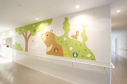 入院生活をそっと励ますかのように、優しいタッチのイラストが描かれた病棟の壁
